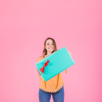 Happy woman holding wrapped gift box against pink background