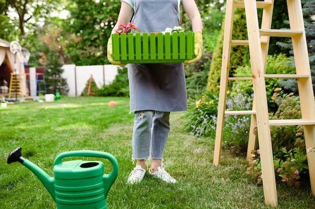 Happy woman holds flower bed in the garden. female gardener takes care of plants outdoor, gardening hobby, florist lifestyle and leisure