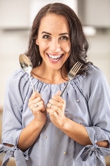 Happy woman holds fork and spoon indoors.