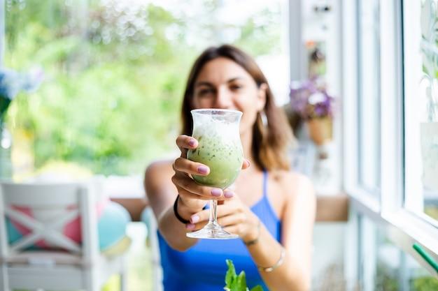 Счастливая женщина держит японский зеленый чай матча со льдом в стакане в кафе женщина со здоровым антиоксидантным напитком в летнем милом кафе