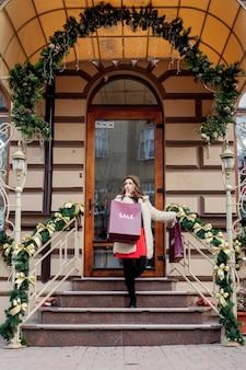 幸せな女性は、クリスマスに販売の店で販売のシンボルと紙袋を保持します