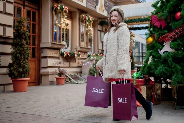 Счастливая женщина держит бумажные пакеты с символом продажи в магазинах с распродажами на рождество,