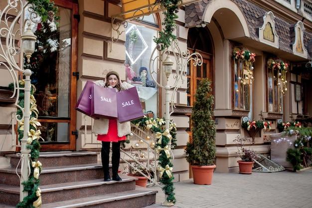 Счастливая женщина держит бумажные пакеты с символом продажи в магазинах с распродажами на рождество