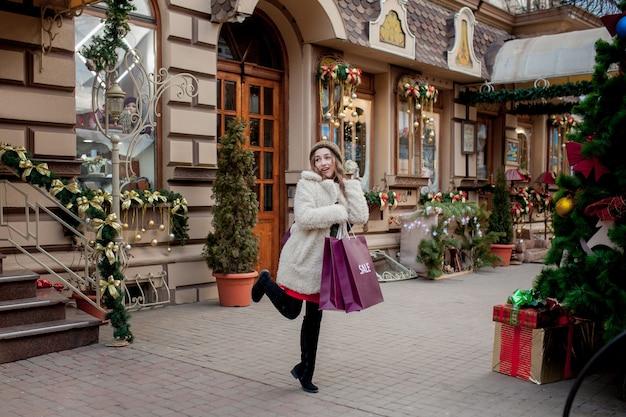 행복 한 여자는 크리스마스에 판매와 함께 상점에서 판매의 상징으로 paperbags를 보유