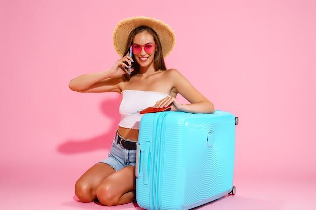 Счастливая женщина держит деньги на паспортные билеты с чемоданом и вызывает такси в концепцию путешествия в аэропорт
