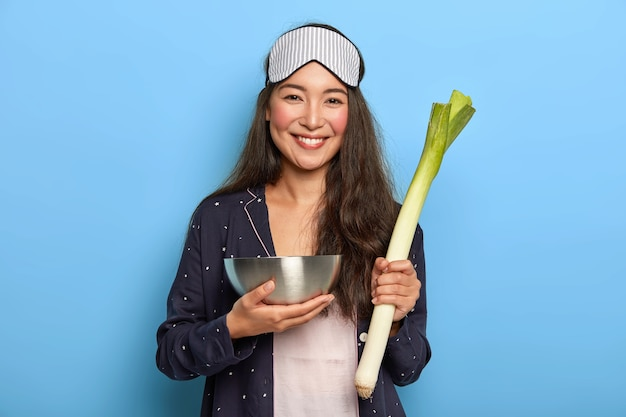 Happy woman holds raw green leek, returns from grocery market