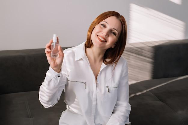 행복 한 여자는 카메라를보고 소독 스프레이 보유하고있다. 성인 여자는 항균 손 청소기를 사용합니다.