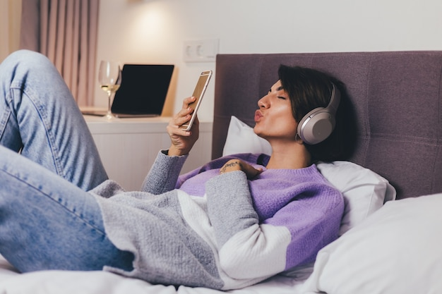Happy woman at home on comfy bed wearing warm clothes pullover, listen music