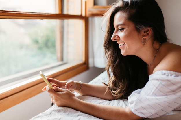 Happy woman at home texting in her phone in bedroom