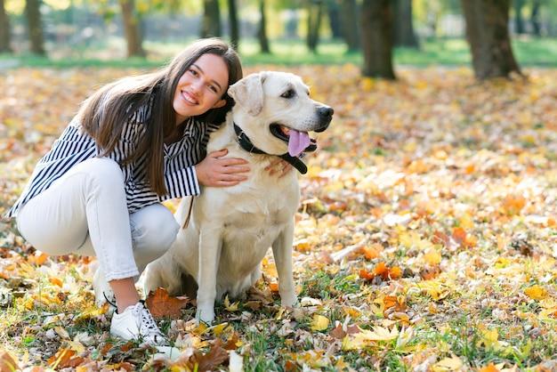 公園で彼女の犬を抱いて幸せな女