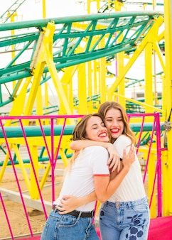 Happy woman hugging her girlfriend in front of roller coaster ride
