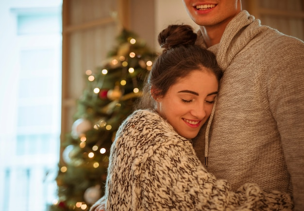 Happy woman hugging man at christmas tree
