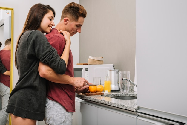 그는 오렌지를 절단하는 동안 행복 한 여자 포옹 남자 뒤에서