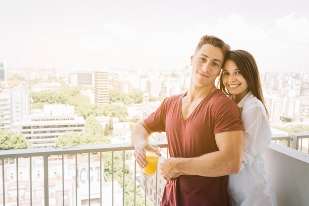 Happy woman hugging man with juice glass on balcony