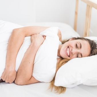 Happy woman hugging pillow while lying on bed