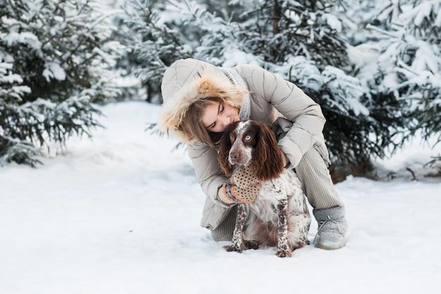 冬の森でチョコレートスパニエルと抱き締めて幸せな女性。