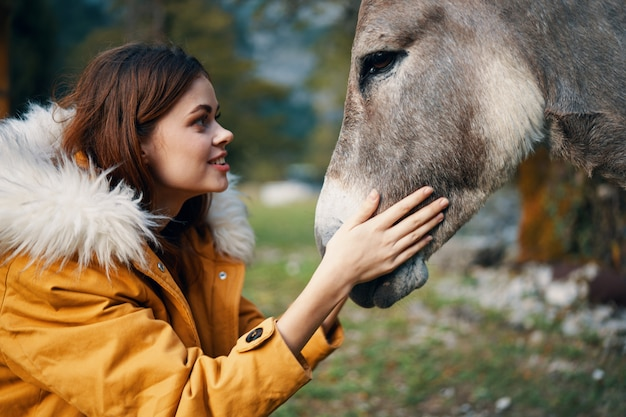 Счастливая женщина обнимает осла в природе крупным планом