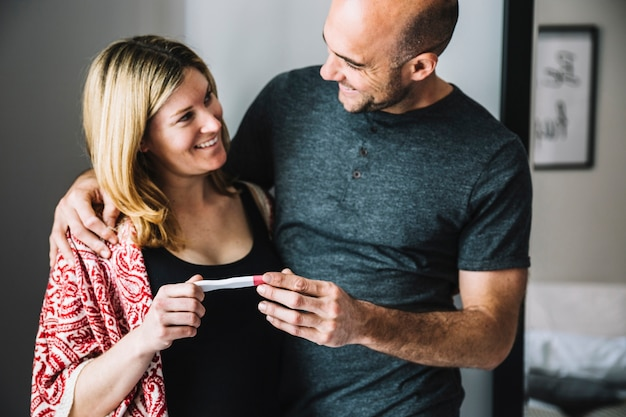 Happy woman and husband looking at pregnancy test