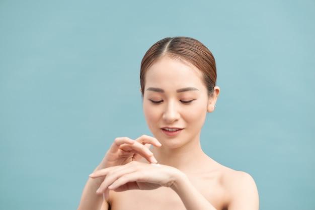 紫の壁に保湿クリームで手の肌に潤いを与える幸せな女性