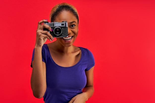 롤빵에 모인 머리를 가진 파란색 티셔츠에 행복한 여자가 사진을 찍습니다