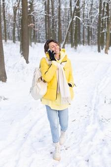 멋진 분위기의 행복한 여자는 눈 덮인 겨울 숲을 산책하고 공원에서 야외에서 시간을 즐기고 전화로 유쾌하게 채팅합니다.