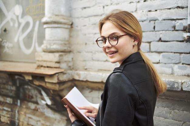 Счастливая женщина в кожаной куртке с книгой в руке