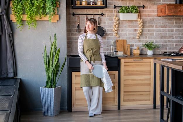 린넨 수건으로 접시를 닦아 싱크대에 의해 부엌에 서있는 린넨 앞치마에 행복한 여자