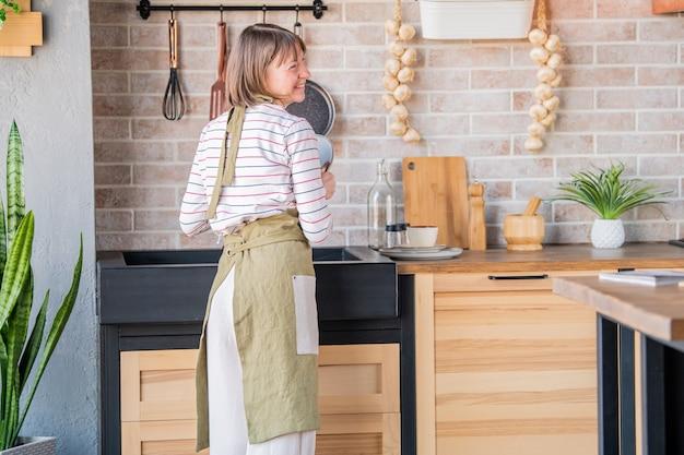 Счастливая женщина в льняном фартуке стоит на кухне у раковины, вытирая тарелку льняным полотенцем
