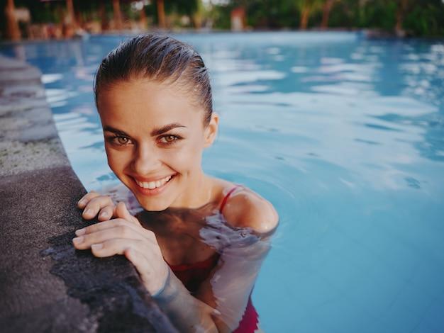 自然の中でプールで泳いでいる間、赤い水着で幸せな女性がいちゃつくと笑顔
