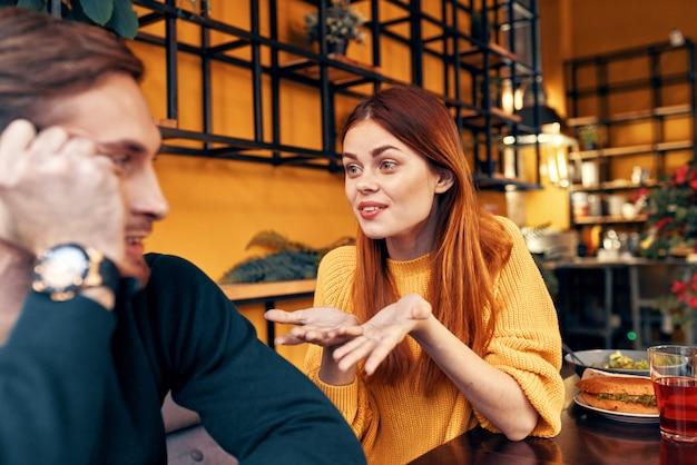 Счастливая женщина в свитере жестикулирует руками, веселые эмоции, а мужчина в свитере сидит в кафе
