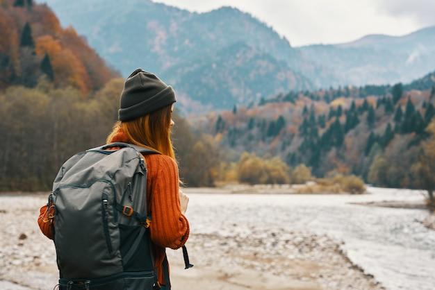 彼女の背中の旅行観光にバックパックと屋外の山の秋の森の幸せな女性