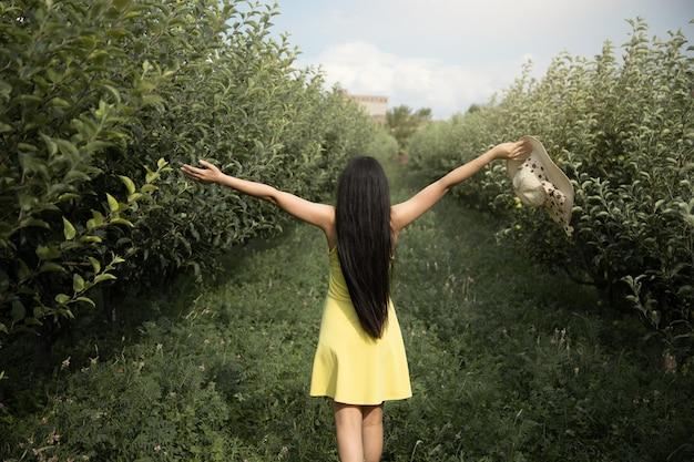 Счастливая женщина сзади в саду