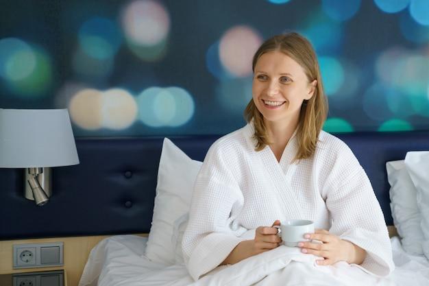 一杯のコーヒー、朝の概念が付いているベッドで幸せな女