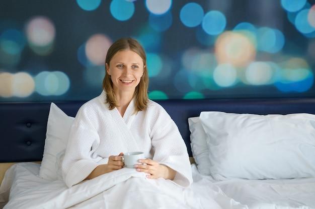 一杯のコーヒーが付いているベッドで幸せな女