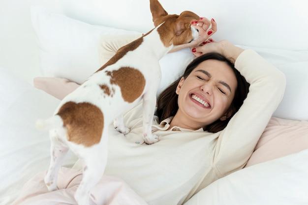 彼女の犬と一緒にベッドで幸せな女