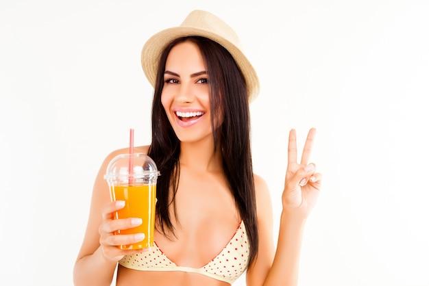 Счастливая женщина в бикини и шляпе держит коктейль и жестикулирует двумя пальцами