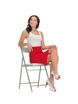 椅子の上の空白の白いtシャツの幸せな女性