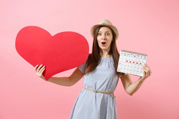 파란 드레스 여름 모자를 쓴 행복한 여성은 비어 있는 큰 붉은 심장, 여성 기간 달력, 배경에 격리된 월경일을 확인합니다. 의료 의료 부인과 개념입니다. 복사 공간