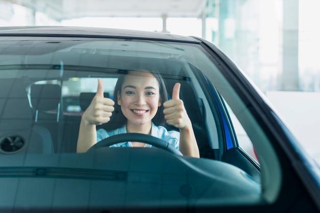 車のディーラーで幸せな女 Premium写真