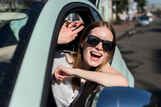 Счастливая женщина в машине собирается путешествовать