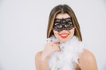 Happy woman in carnival mask wearing boa feather on white background