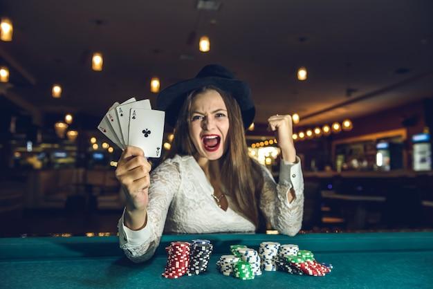 4つのエースを保持しているカジノで幸せな女性
