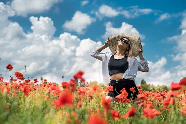 양 귀 비의 분야에서 캐주얼 옷감에 행복 한 여자는 무료 여름 시간을 즐길 수 있습니다. 자연