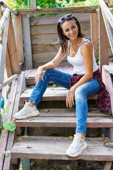 カジュアルな服を着た幸せな女性がベランダの階段に座って、白人の女の子を笑顔で...