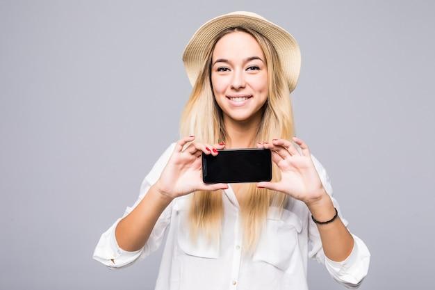 회색 벽에 빈 스마트 폰 화면을 보여주는 캐주얼 옷에 행복 한 여자