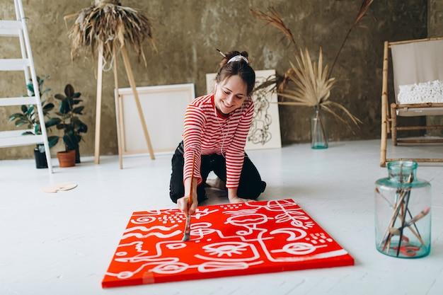 Счастливая женщина в повседневном наряде, используя кисть для рисования на красном холсте с белым цветом