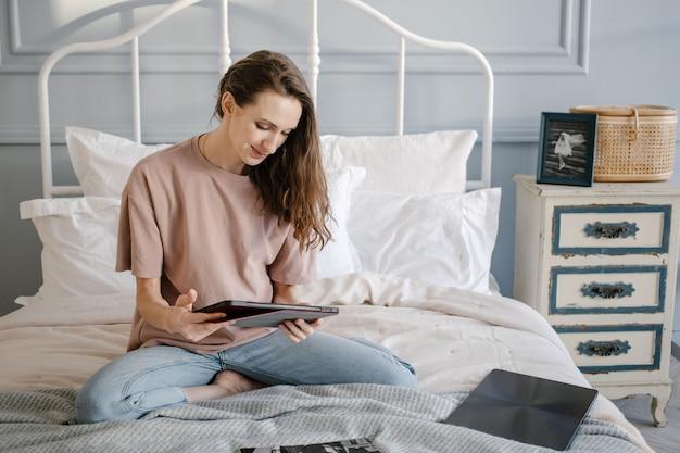 ベッドの上で自宅から離れた場所でラップトップで作業しているヘッドフォンでカジュアルに幸せな女性