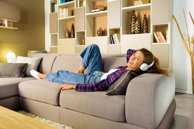 체크 셔츠와 청바지 거실에서 소파에 편안하고 흰색 귀에 헤드폰으로 음악을 듣고 행복한 여자