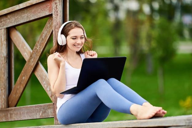 Счастливая женщина в беспроводных наушниках болтает в ноутбуке на открытом воздухе