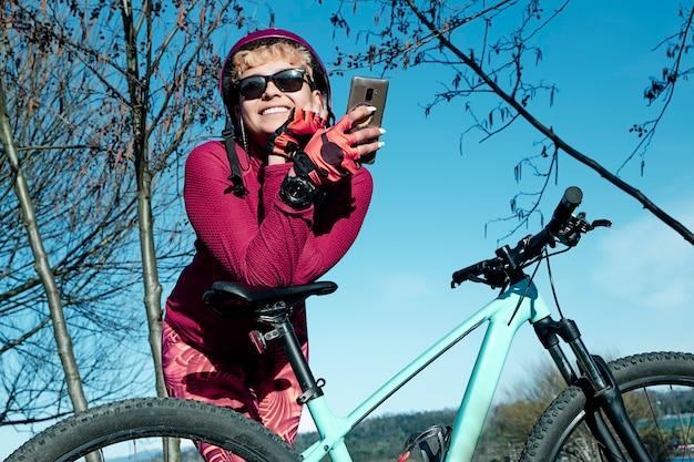 湖の近くで休んでいるスマートフォンを使用して自転車でヘルメットをサイクリングで幸せな女性